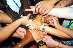 Arms outstretched towards the center of a group of people with their hands clasping one-another